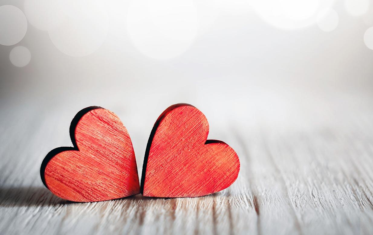 Valentinstag – rote Herzen auf grauem Holz